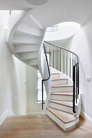 White-painted spiral staircase with wooden treads and black metal balustrade