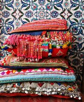 Colourful woven cushions with beaded fringes and sequins against floral Moroccan wall tiles