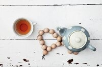 Retro teapot on hand-crafted coaster of wooden beads and cup of tea