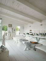 Minimalist, modern lake house with interior painted entirely white; set table with sheepskin blankets on wooden bench