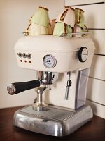 Stacked, vintage coffee cups on top of cream-coloured, retro espresso machine on kitchen worksurface
