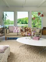 Comfortable living room with sofa, white coffee table, retro-style standard lamp and view of lake