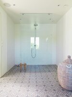 Spacious, modern shower area with rainfall shower, glass screen and floral-patterned cement tiles on floor