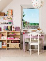 Girl's bedroom with pink desk, white wooden chair and open-fronted toy shelves