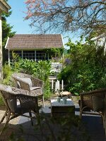 Idyllic seating area on terrace with wicker furniture and view of summer garden