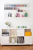 Sideboard with doors and open-fronted modules on castors below white String shelves on wall