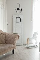 Beige, antique sofa, removed door and white rocking horse in vintage-style interior