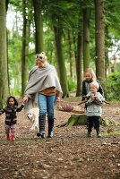Family with dog going on autumnal picnic in woods