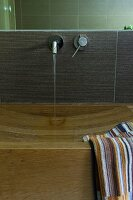 Elegant wooden washstand with carved sink, striped towel and water running from wall-mounted tap