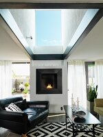 Black leather armchair and coffee table in front of fireplace in living room with large skylight
