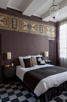Double bed in bedroom with chequered floor and Art-Nouveau frieze on purple-painted wall