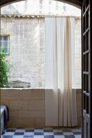 Balcony with airy curtain in arched opening