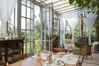 Antique furniture, floral crockery on dining table and wicker chairs in seating area in vintage-style conservatory
