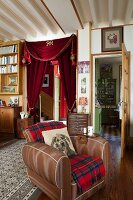 Antique furniture, curtain on doorway and dog-motif scatter cushion on leather armchair in classic living room