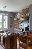 Open-plan country-house kitchen with dining area in restored interior