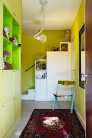 Hallway with light green fitted shelves and white fitted cupboards in front of stairs