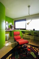 Red designer couch in office with green fitted furnishing and black patterned rug
