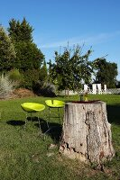 Tree trunk used as garden table and two neon yellow bar stools in summer garden