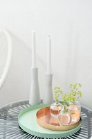 Vases of leaves on copper and turquoise trays in front of candles in white ceramic candlesticks