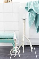 Candlesticks made from branches painted white on grey-tiled floor, turquoise towels on footstool and edge of bathtub