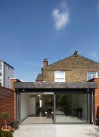 One-storey, modern extension in back yard of traditional, British brick house