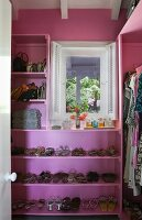 Walk-in wardrobe painted pink with integrated shoe rack and handbag shelf