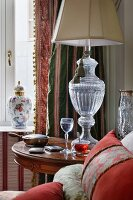 Lamp with urn-style glass base on antique side table, lidded china vase and classic, traditional curtains on window