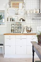 Detail of kitchen counter with white base units below plate rack on partially tiled wall