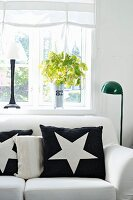 Black cushion with white star motif on white sofa next to standard lamp