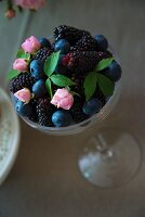 Berries and small rosebuds in dessert glass
