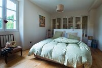 Double bed with lime green bed linen and fitted wardrobe with lattice doors in simple bedroom