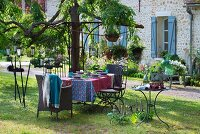 Set garden table, wicker and metal chairs, vintage candle lanterns and candlesticks