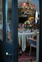 View through half-open door of festively set table and elegant chandelier with pink lampshades