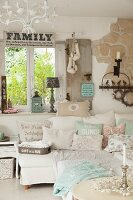 Detail of sofa with collection of pastel scatter cushions in shabby-chic interior