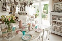 Dining table set with romantic pastel crockery in open-plan shabby-chic kitchen