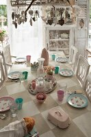 Chandelier decorated with pendants above table with painted chequered top and pastel, shabby-chic crockery