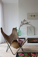 Butterfly chair with pale brown suede cover in front of low sideboard
