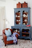 Old-fashioned crockery in blue vintage dresser and brown leather armchair on old wooden floor