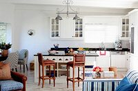 Bright country-house kitchen with island counter, brown bar stools and blue accessories