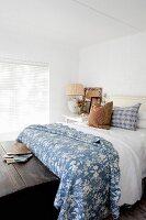 Rustic blue and white bedroom with old wooden trunk at foot of bed