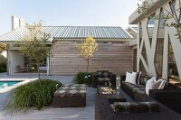 Modern, dark wicker outdoor furniture on spacious terrace