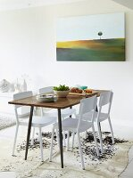 Simple dining table and white chairs on cowhide rug and modern landscape painting on wall