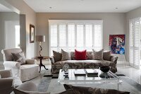 Various upholstered seating, louvre blinds and plexiglas coffee table in classic living room
