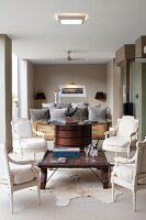 Four white Baroque-style chairs around Colonial-style coffee table in front of Art Deco table