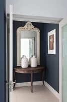 View through open double doors of console table and white wood-framed mirror on dark blue hall wall