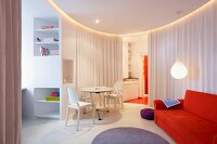 Orange sofa, white Ghost chairs and table in circular living area with curtains as partitions in modern interior