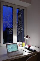 Laptop next to roll of paper and desk lamp on table below decorated window at twilight