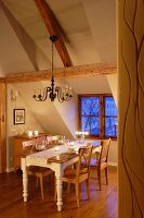 Dining area in attic with exposed wooden roof beams