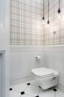 Toilet mounted on wainscoting below Bulb lamps against tartan wallpaper
