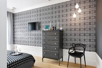 Dark grey chest of drawers and black chair against grey and black tartan wallpaper in bedroom